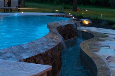 Water feature by pool with outdoor lighting